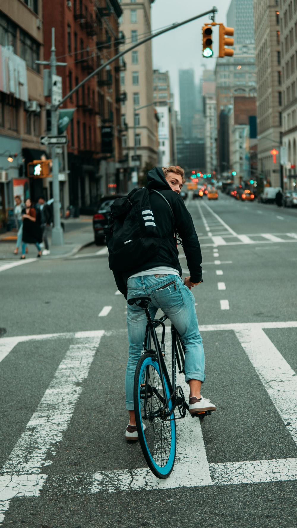 man in black jacket and blue denim jeans riding bicycle on road during daytime
