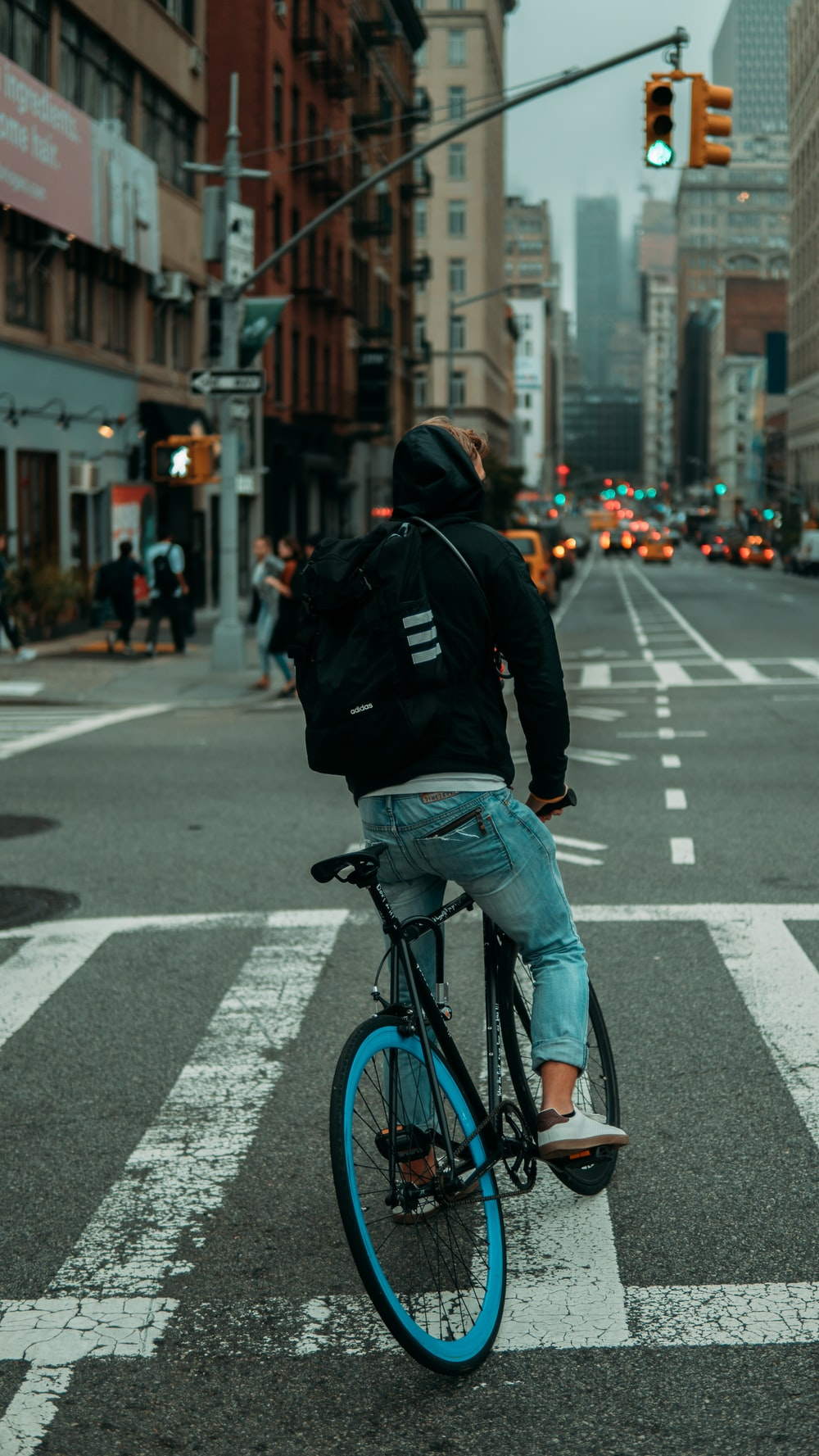 man in black jacket and blue denim jeans riding on bicycle on road during daytime