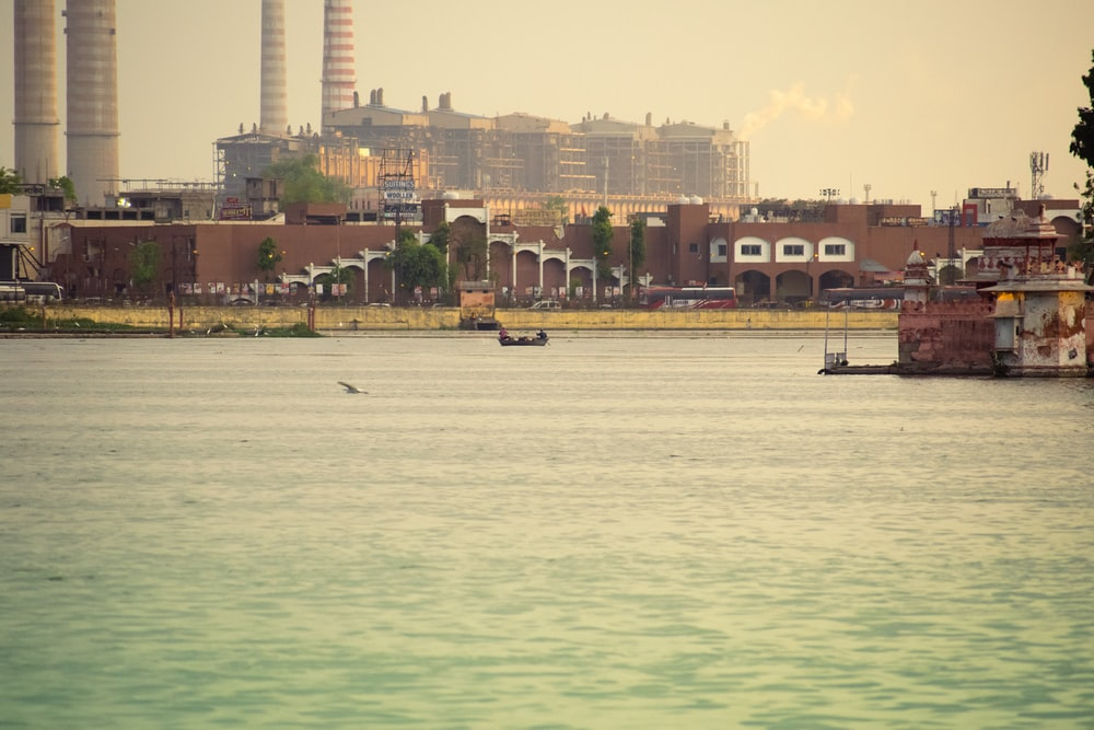 people riding boat on sea near high rise buildings during daytime