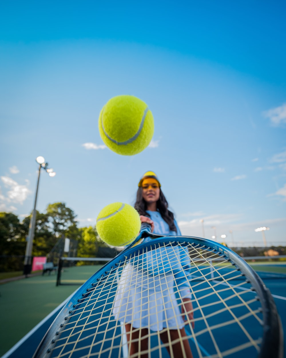 woman in black jacket and black pants holding tennis racket under blue sky during daytime