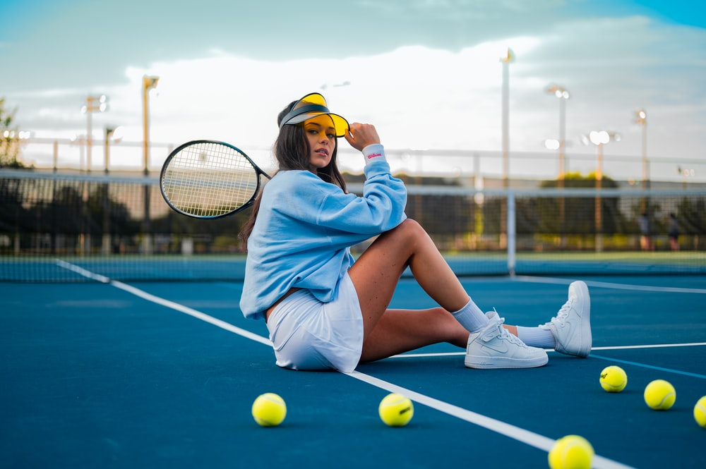 woman in blue dress sitting on tennis court