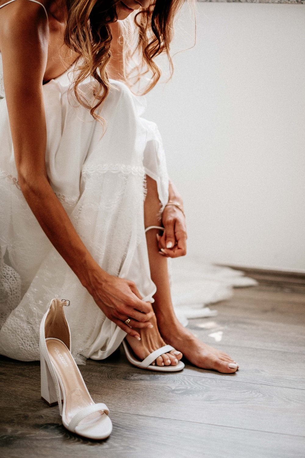 woman in white dress wearing white leather peep toe pumps