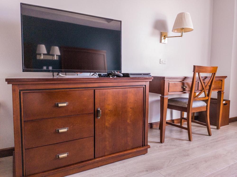 black flat screen tv on brown wooden drawer