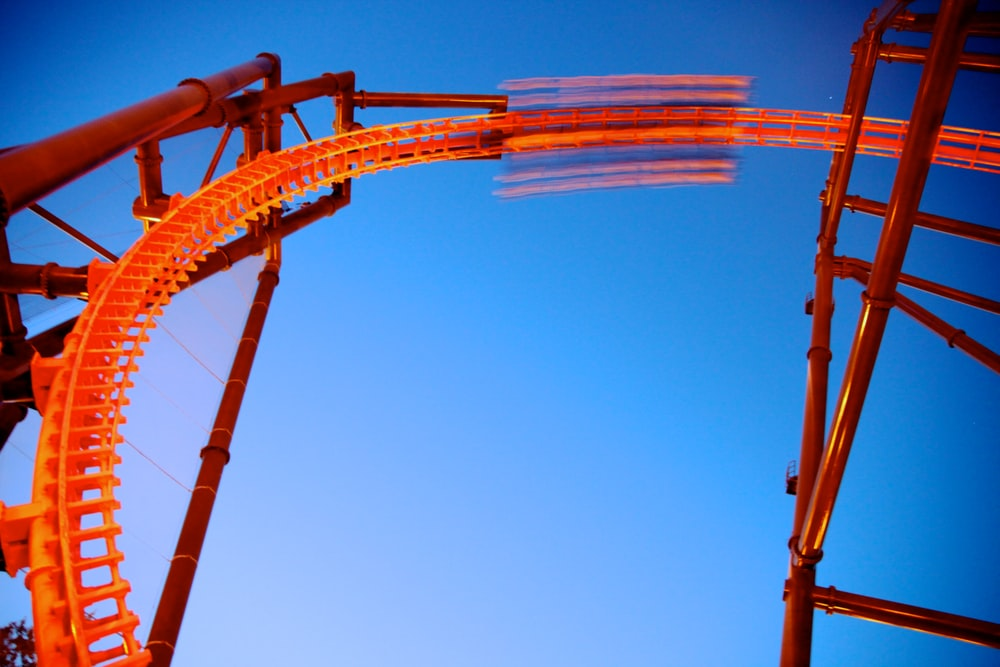 orange and white roller coaster under blue sky during daytime