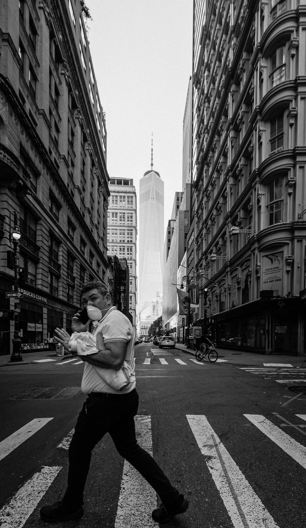 man in white long sleeve shirt and black pants sitting on sidewalk in grayscale photography