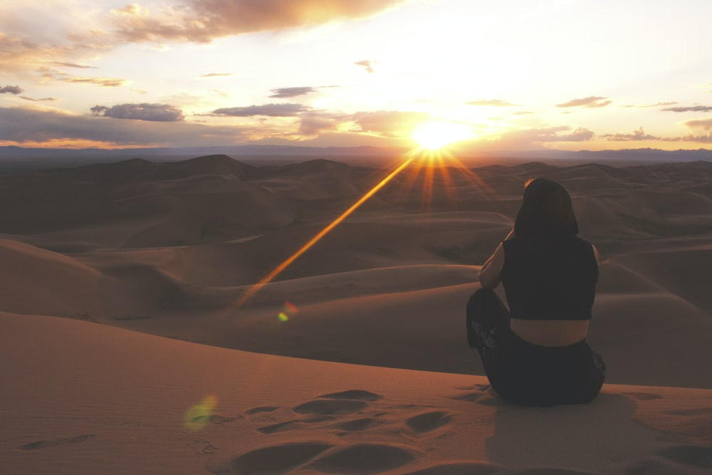 woman in black jacket sitting on sand during sunset