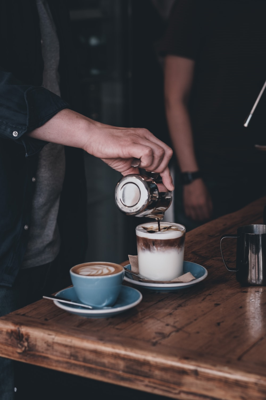 person pouring milk on white ceramic mug