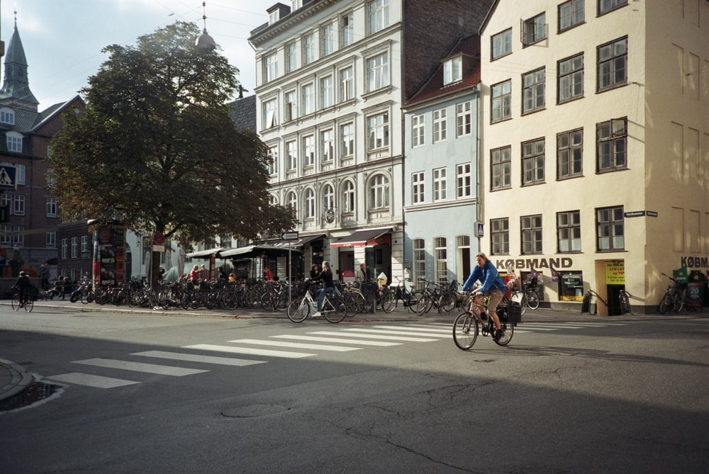 people riding bicycles on road near building during daytime
