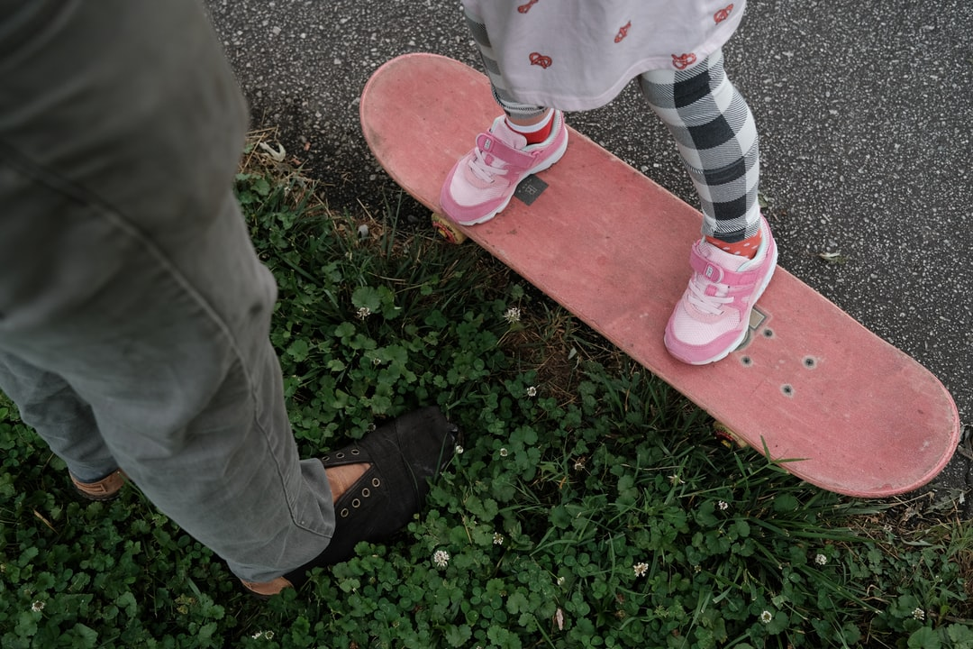 A Dad and his daughter playing together on a skateboard.