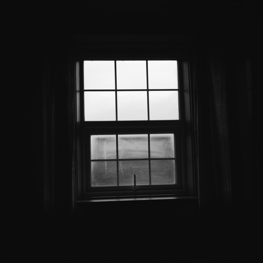 grayscale photo of window with white frame