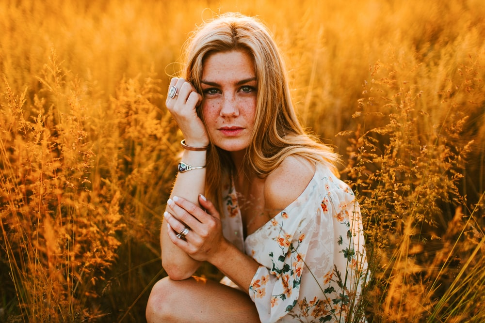 woman in white and brown floral dress sitting on brown grass field during daytime