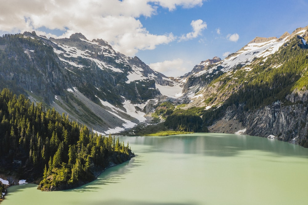 lake in the middle of green and brown mountains under blue sky and white clouds during