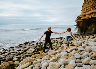 2 women in black tank top and blue denim jeans standing on rocky shore during daytime