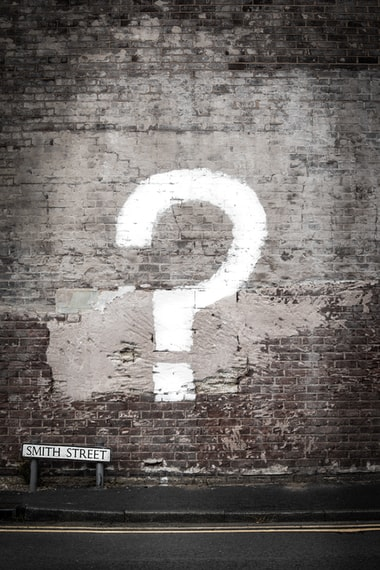 Question mark painted on a brick wall