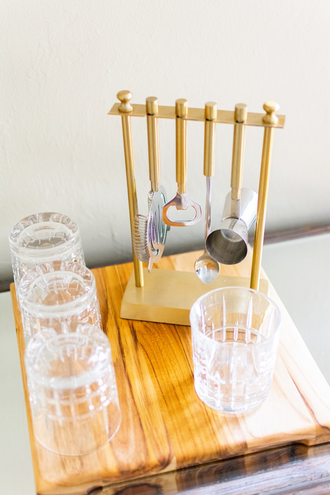 Golden cocktail bar set and glasses on wood square