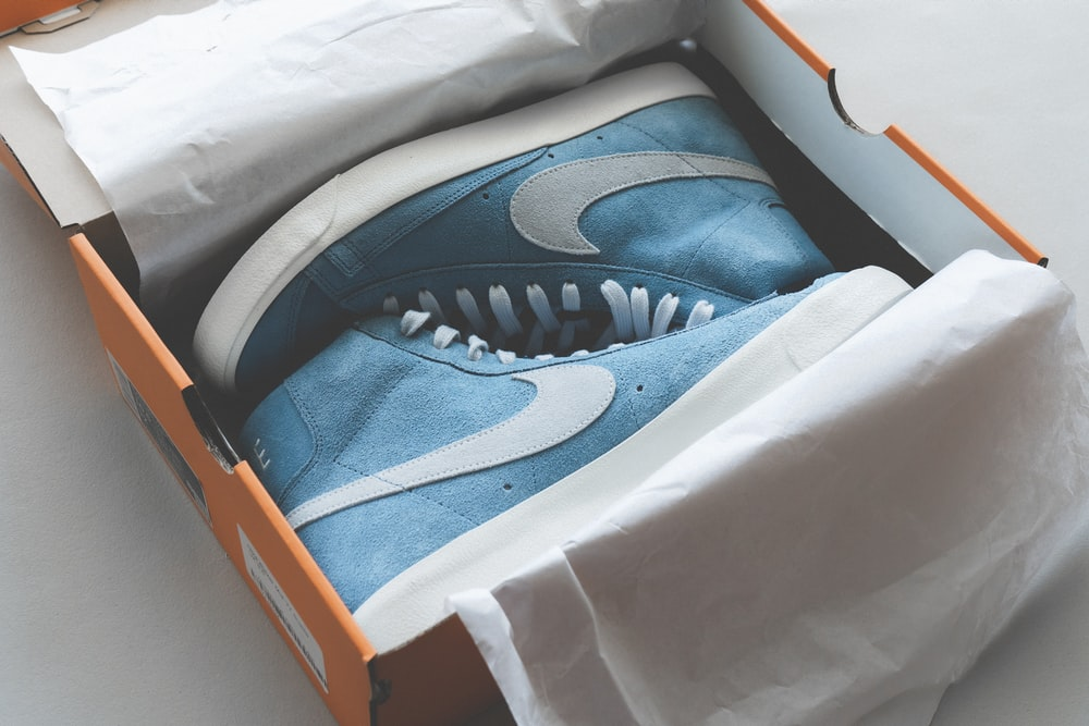 blue and white nike athletic shoes in box
