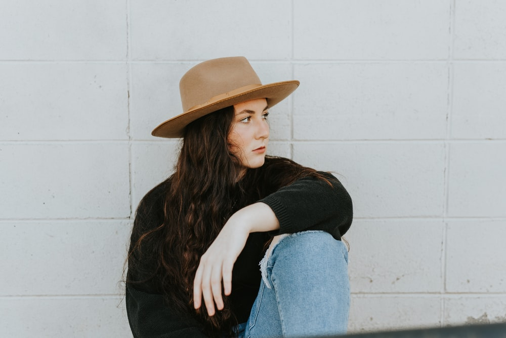 woman in black long sleeve shirt and blue denim jeans wearing brown fedora hat sitting on with with with on