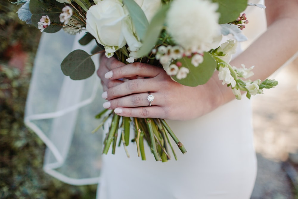 person holding white and green flower bouquet