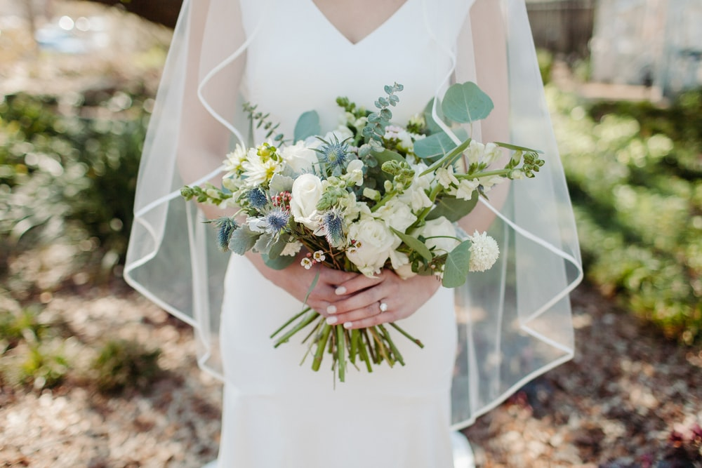 woman in white wedding dress holding white flower bouquet