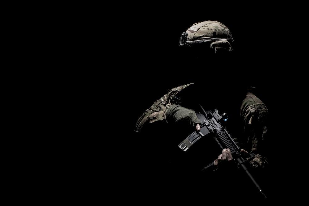 man in black helmet holding rifle