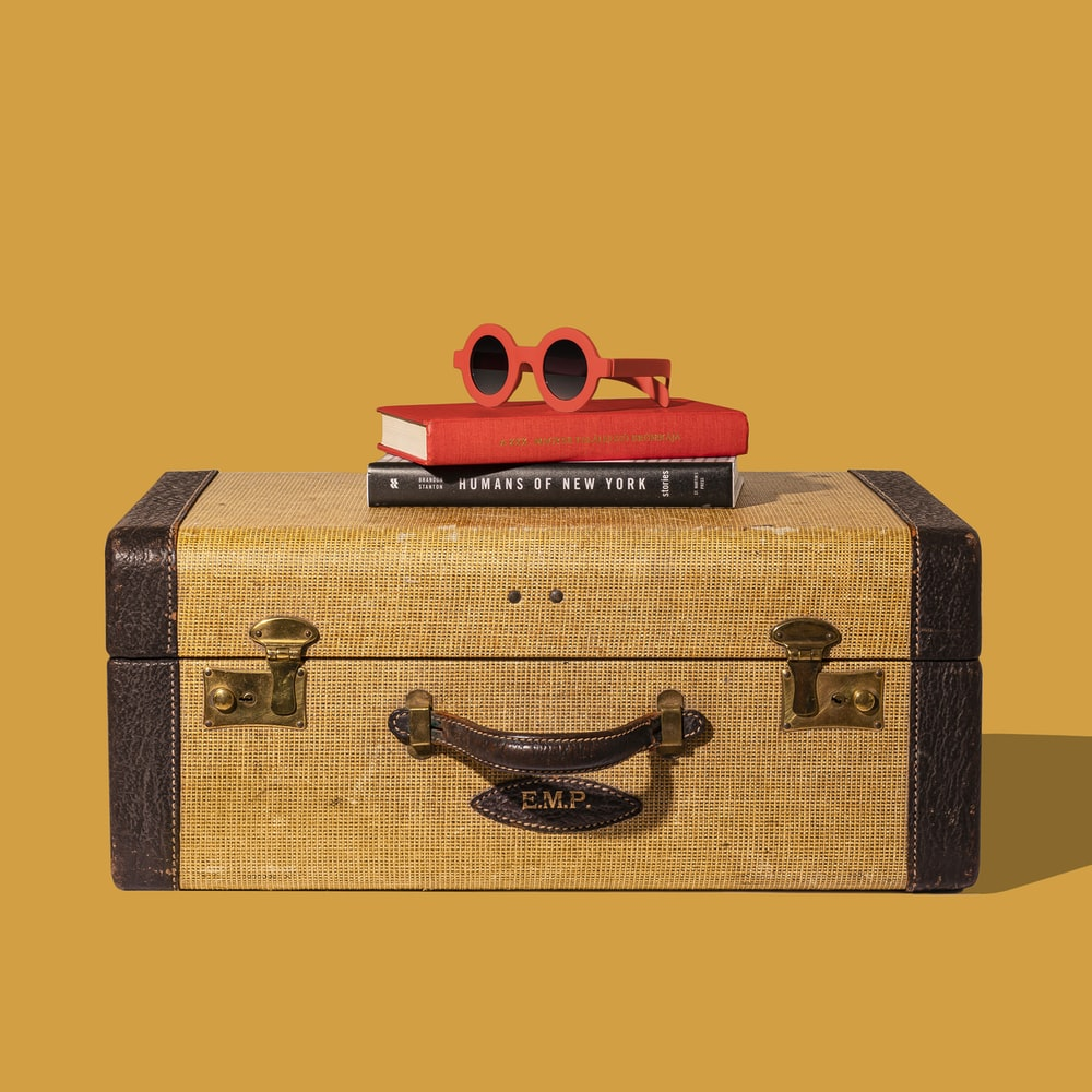 brown and black suitcase with red and yellow plastic toy