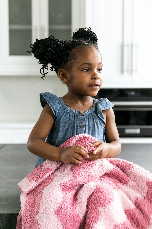 girl in gray sleeveless shirt sitting on floor