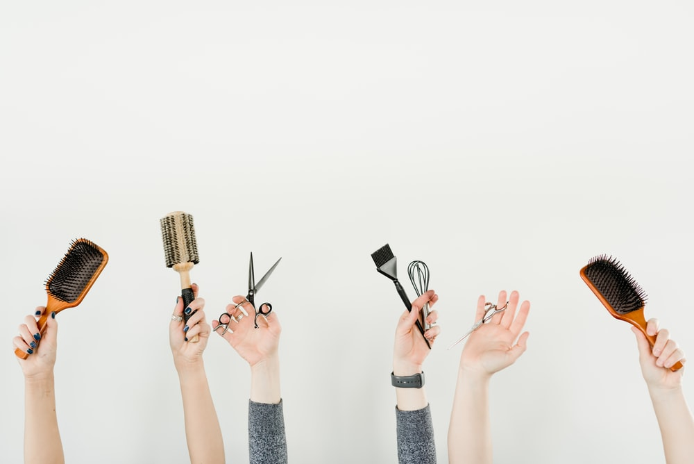 person holding silver and black hair brush
