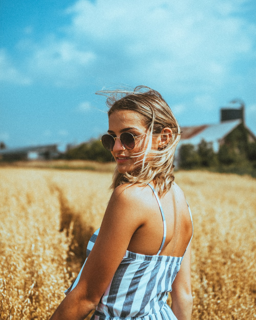 woman in white and black stripe tank top wearing sunglasses standing on brown grass field during
