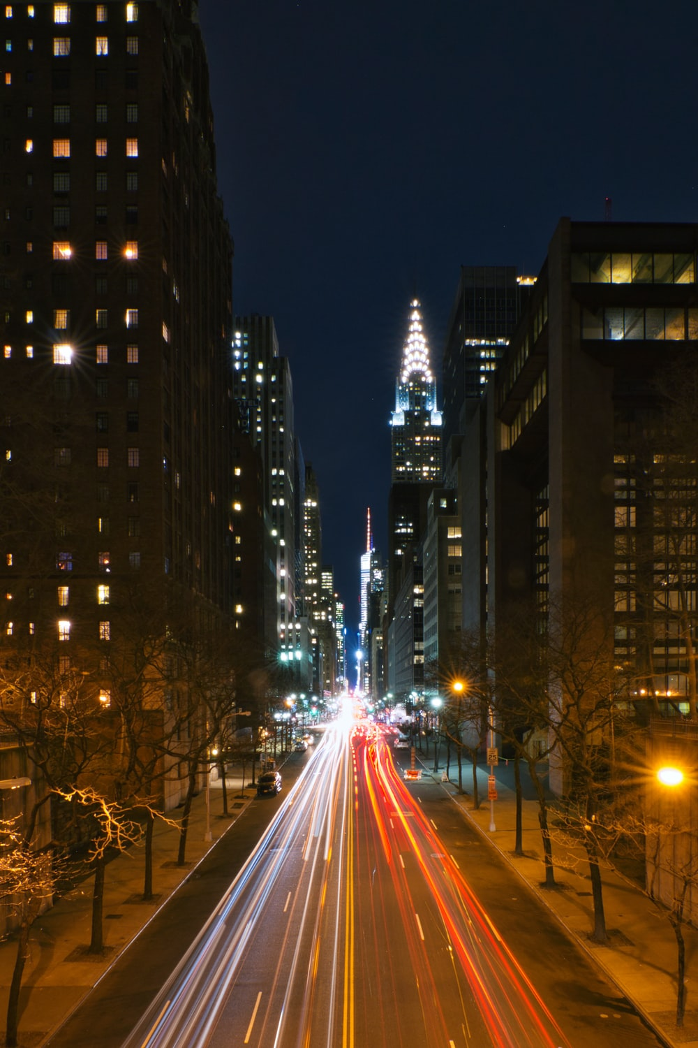 cars on road between high rise buildings during night time