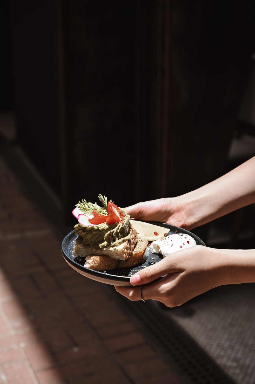 person holding a white ceramic bowl with food