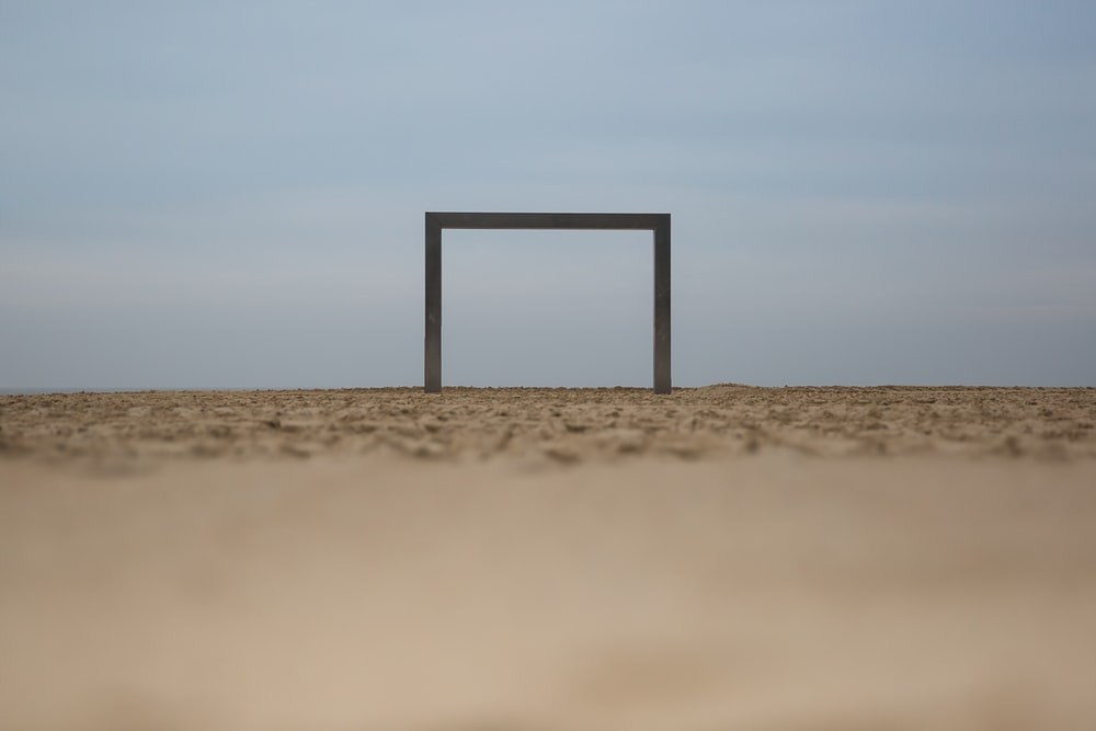 brown wooden stand on brown sand during daytime