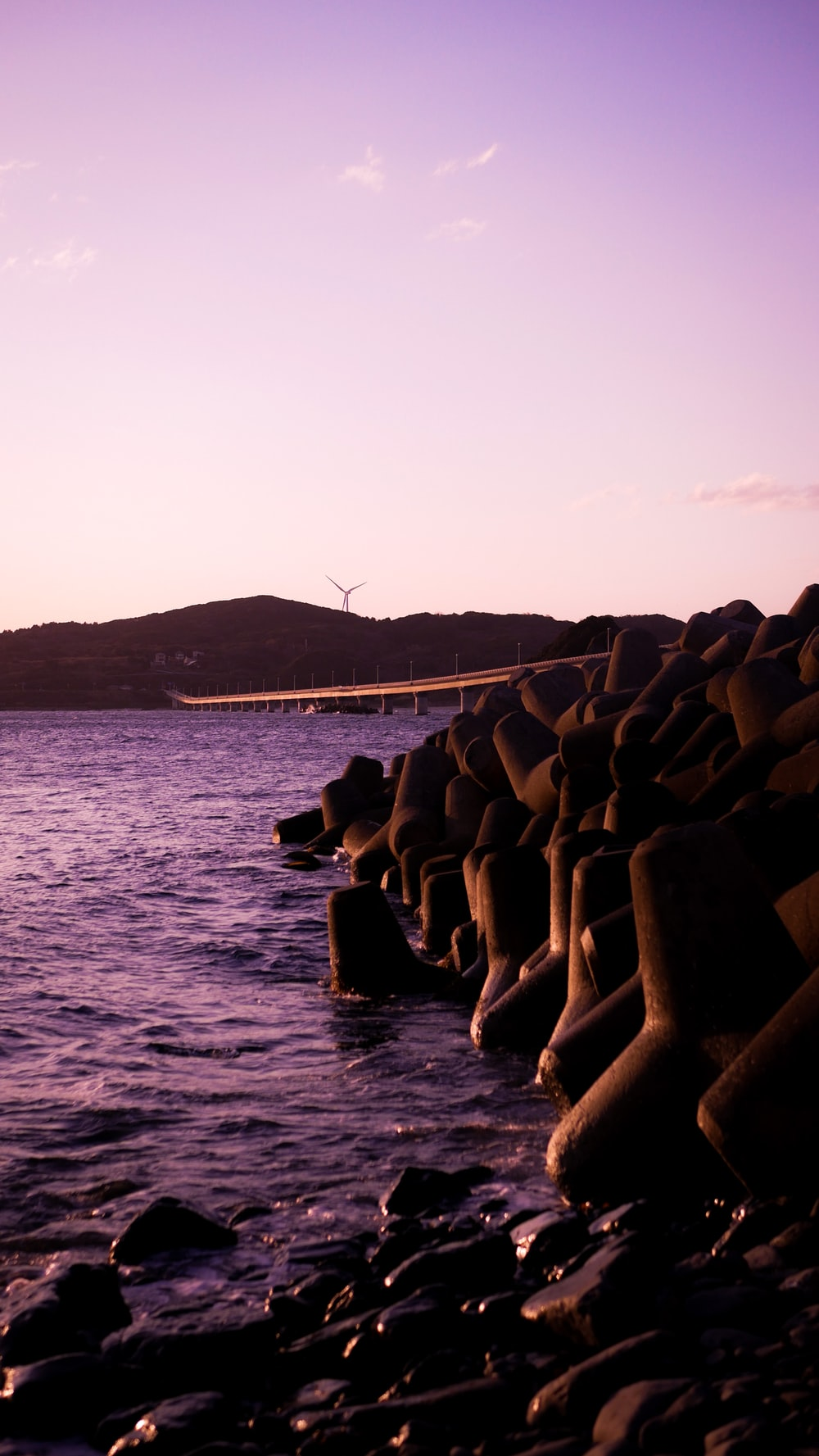 gray concrete blocks on sea shore during daytime