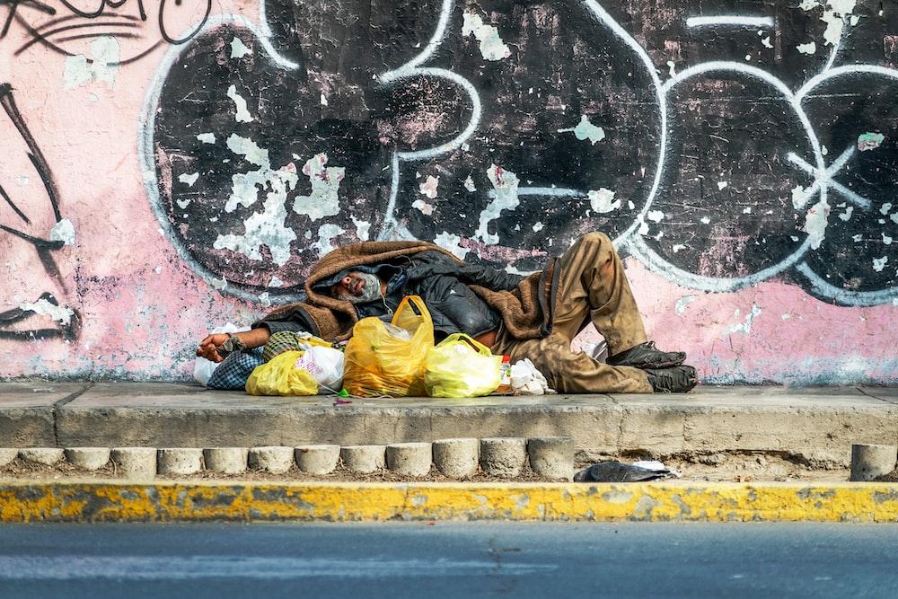 man in yellow jacket lying on concrete floor