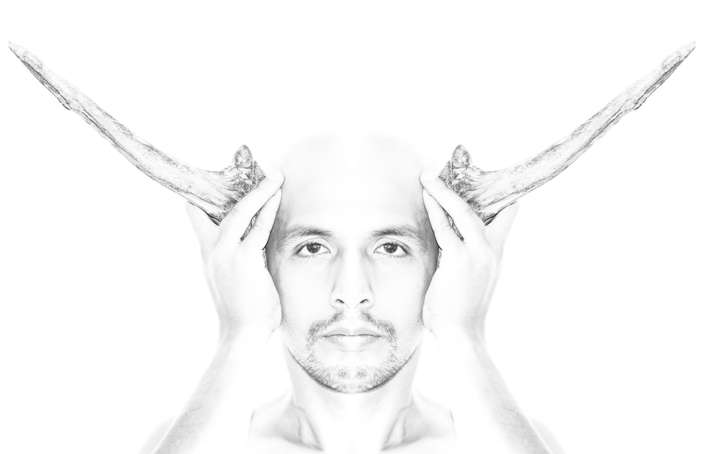 grayscale photo of man with right hand on head
