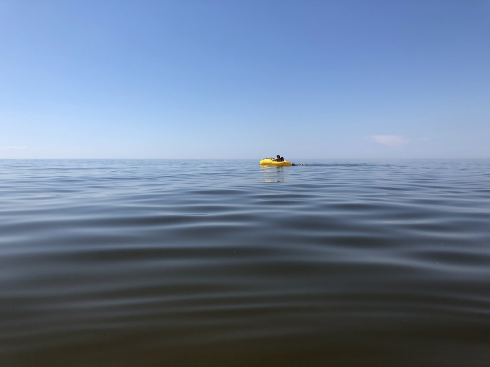 yellow and white boat on sea during daytime