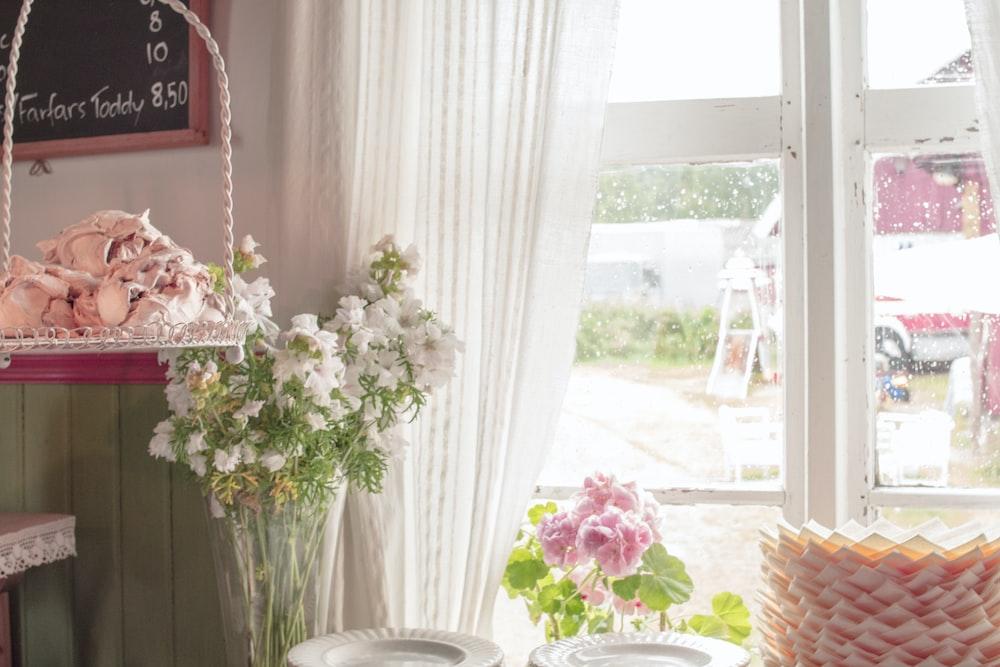 white and pink flowers on white ceramic vase