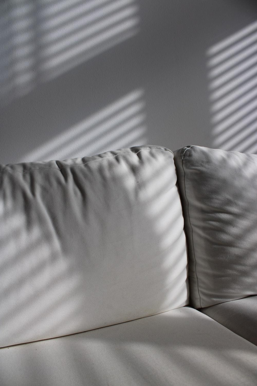 white leather sofa near white wall