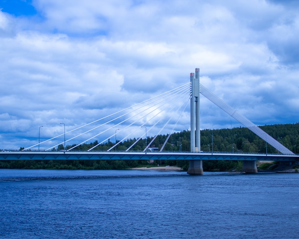 white bridge over the sea under white clouds and blue sky during daytime