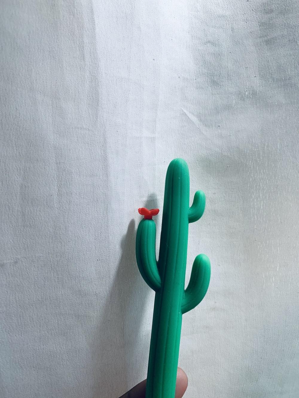 green plastic toy on white textile