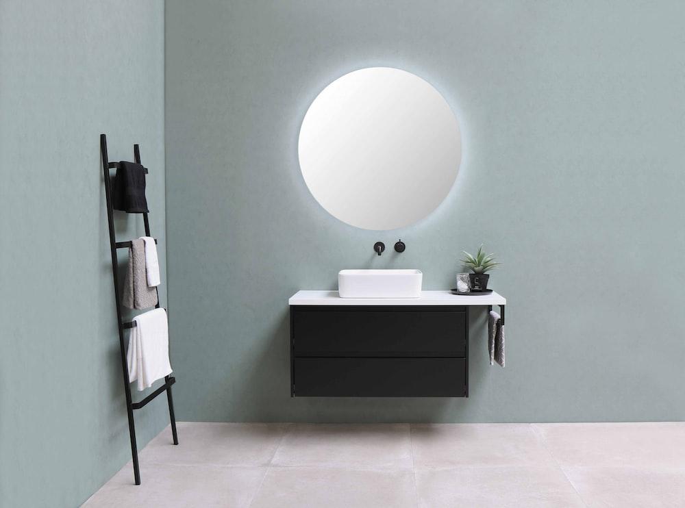 white round mirror on green wall