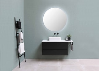 white round mirror on green wall