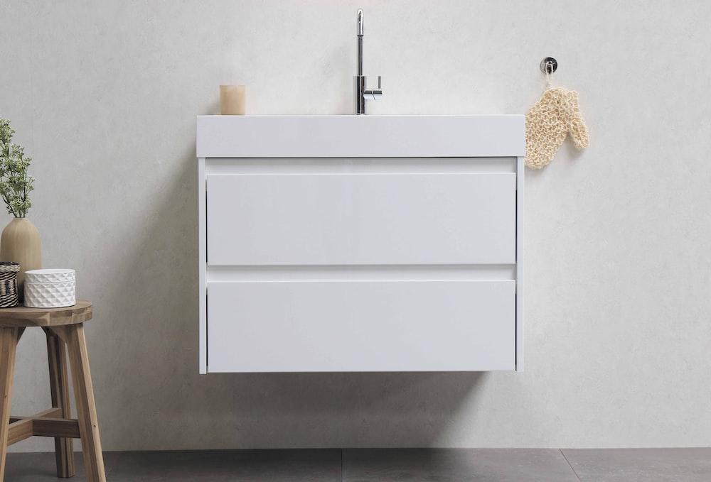 white wooden cabinet on white ceramic tiles