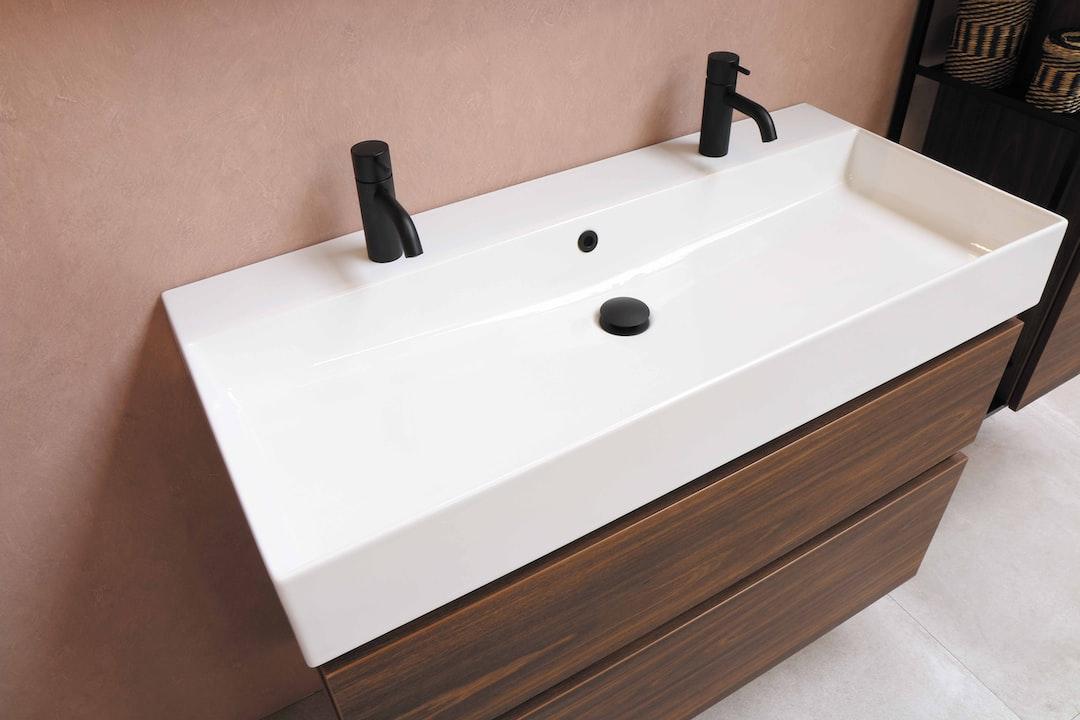 black plastic faucet on white ceramic sink