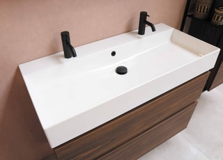 black plastic faucet on white ceramic sink