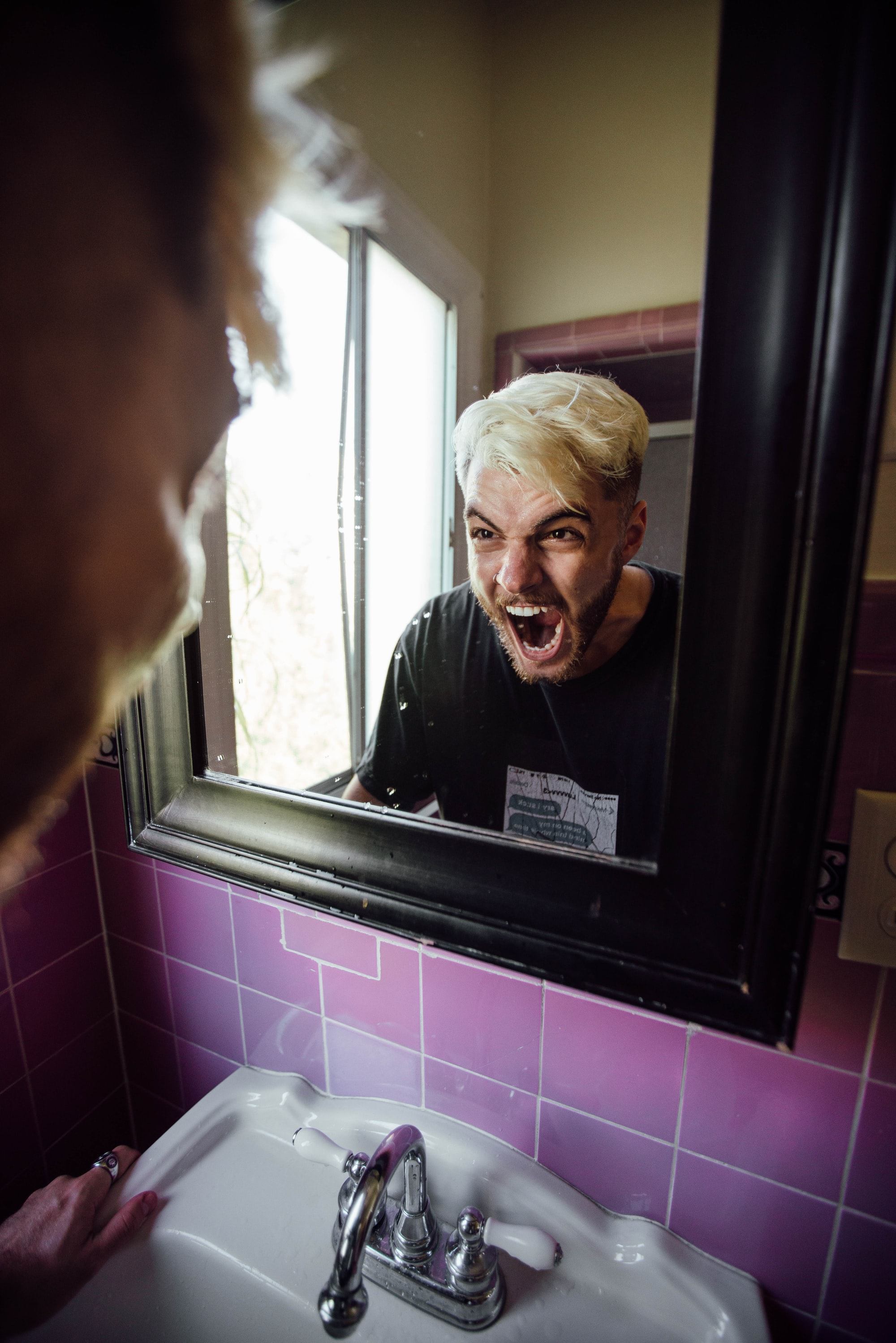 Man screaming at himself in the bathroom.