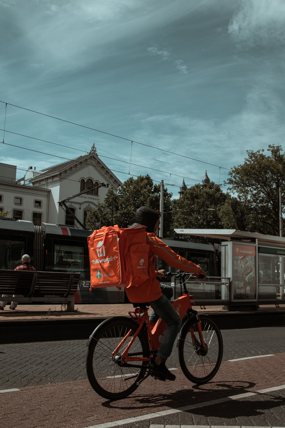 man in red long sleeve shirt riding bicycle on road during daytime