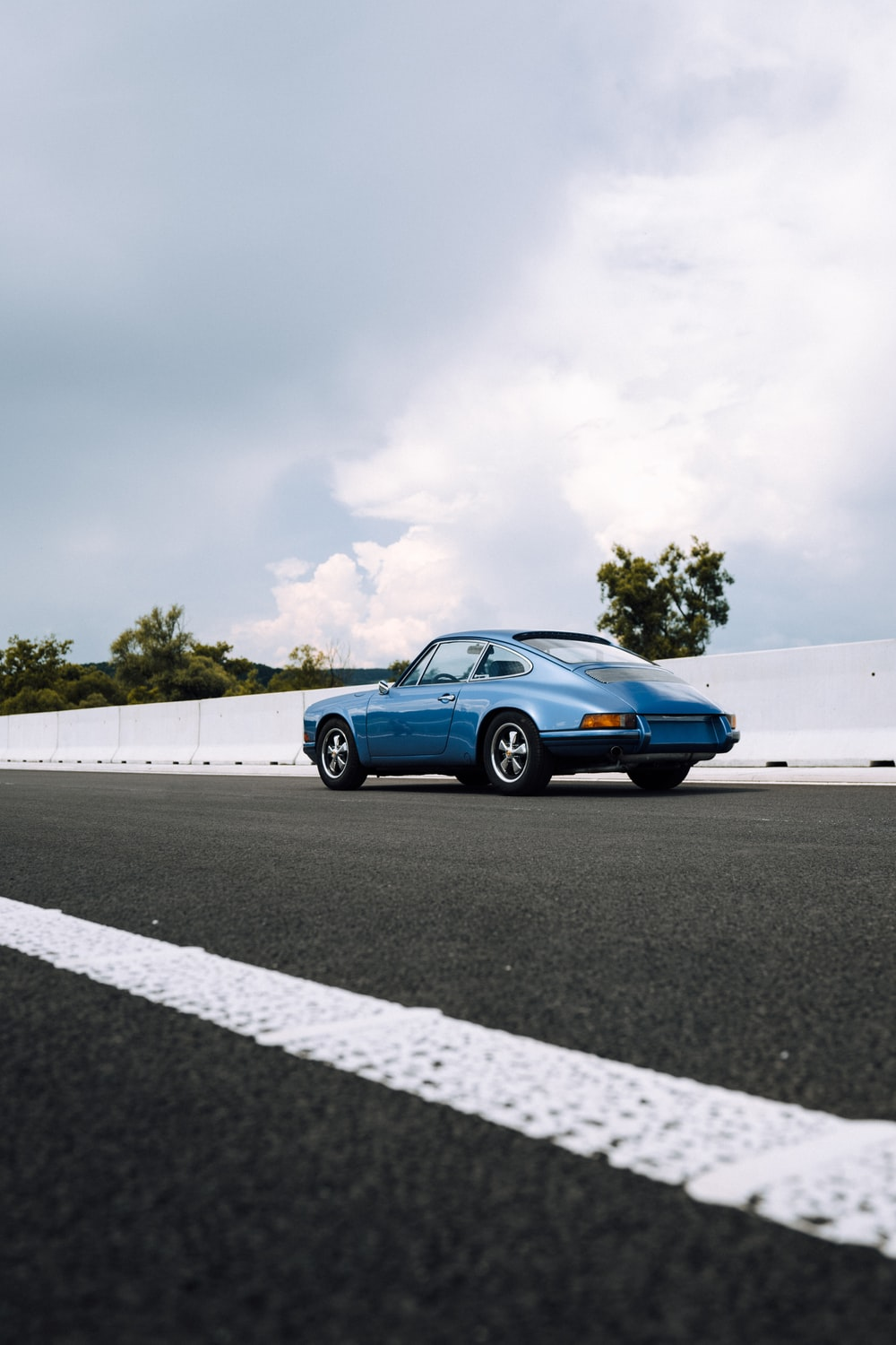 blue coupe on gray asphalt road under white cloudy sky during daytime