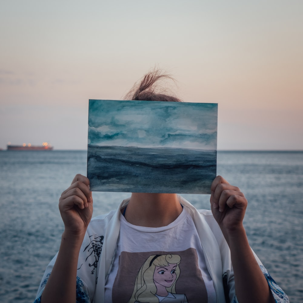 woman in white crew neck t-shirt holding blue and white painting