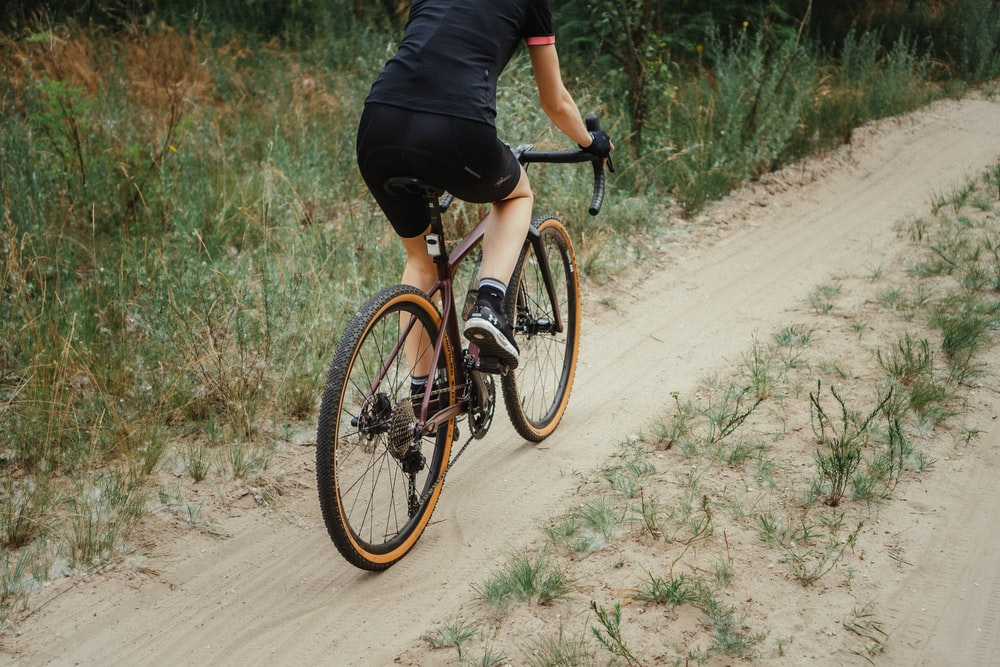man in black shirt riding on black and white road bike