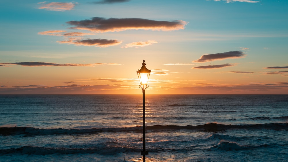 silhouette of lamp post on seashore during sunset